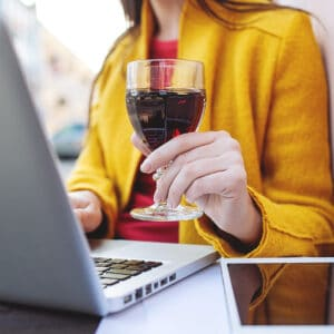 Image for the newsletter section with a lady working on a laptop holding a galss of wine.